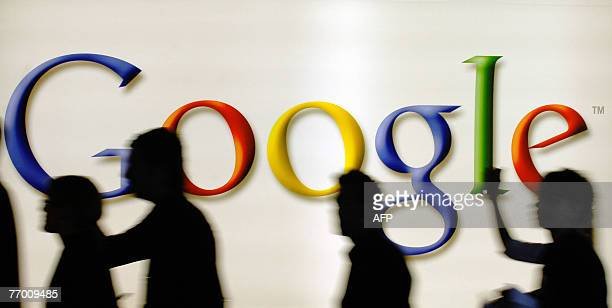 Visitors walk past the logo of internet search engine giant Google at the trade fair for digital marketing OMD 25 September 2007 in Dusseldorf The...