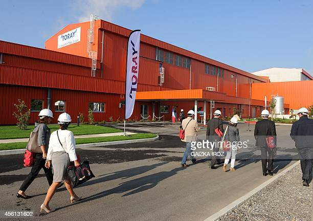 Visitors walk past the new plant of Tokyobased carbon fiber producer Toray Industries during its inauguration in Lacq on September 26 2014 AFP PHOTO...