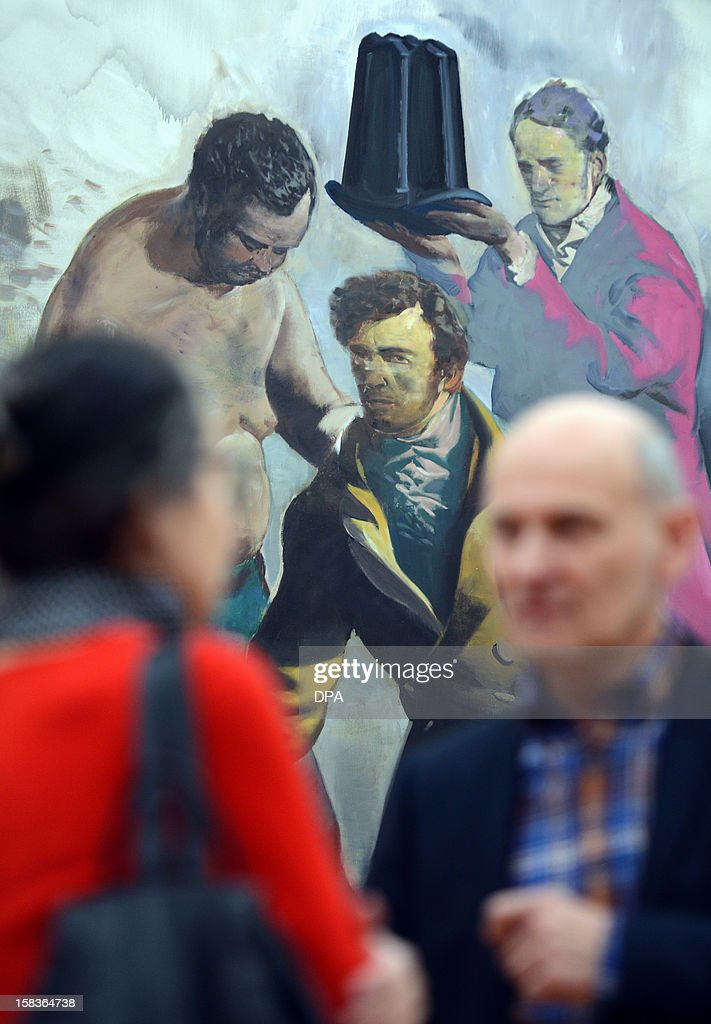 Visitors walk past the painting 'Die Kroenung' (The Coronation) by German artist Neo Rauch during a preview of a double exhibition with works by Rauch and his wife at the Kunstsammlungen Chemnitz museum in Chemnitz, eastern Germany, on December 14, 2012. From December 16, 2012 to February 10, 2013, the museum will present simultaneously the show 'Gravitation' with works by Rauch's wife Rosa Loy and the show 'Abwaegung' (consideration) with works by Neo Rauch.