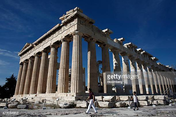 Visitors walk past the Parthenon temple on Acropolis Hill in Athens Greece on Sunday May 3 2015 Greece and its international creditors remain apart...