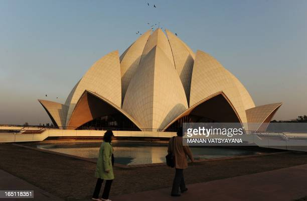 Visitors walk past the pond at the Lotus Temple in New Delhi on February 3 2010 The Bahá'í House of Worship popularly known as the Lotus Temple due...