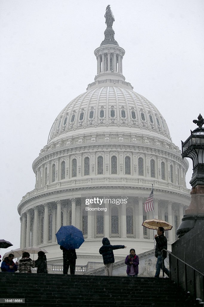 Visitors walk past the U.S. Capitol while holding umbrellas in Washington, D.C., U.S., on Monday, March 25, 2013. An early spring snowstorm tied up air traffic along the U.S. East Coast, threatening to bring 3 inches (7.6 centimeters) of slushy snow to the large cities from Washington to New York. Photographer: Andrew Harrer/Bloomberg via Getty Images