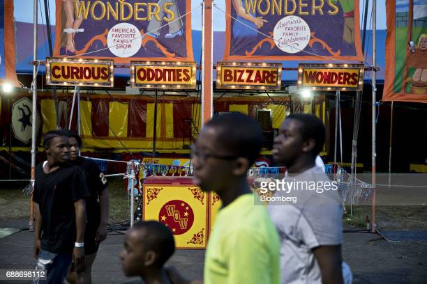 Visitors walk past the World of Wonders tent during the Dreamland Amusements carnival in the parking lot of the Neshaminy Mall in Bensalem...