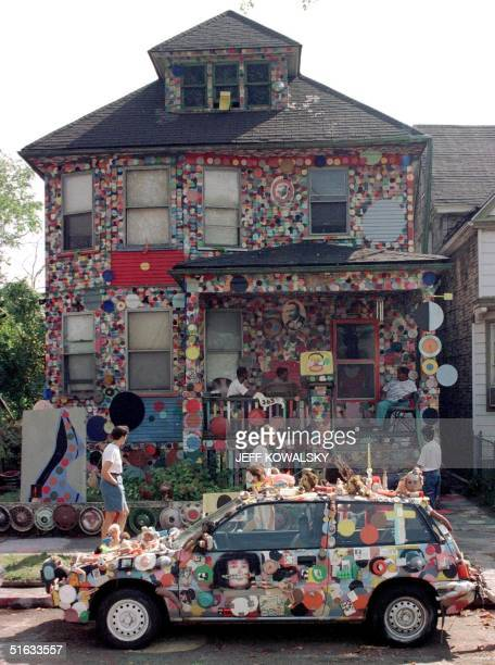 Visitors walk past the``Dotty Wotty House'' 26 September part of the Heidelberg Project in Detroit which officials are trying to tear down Artist...