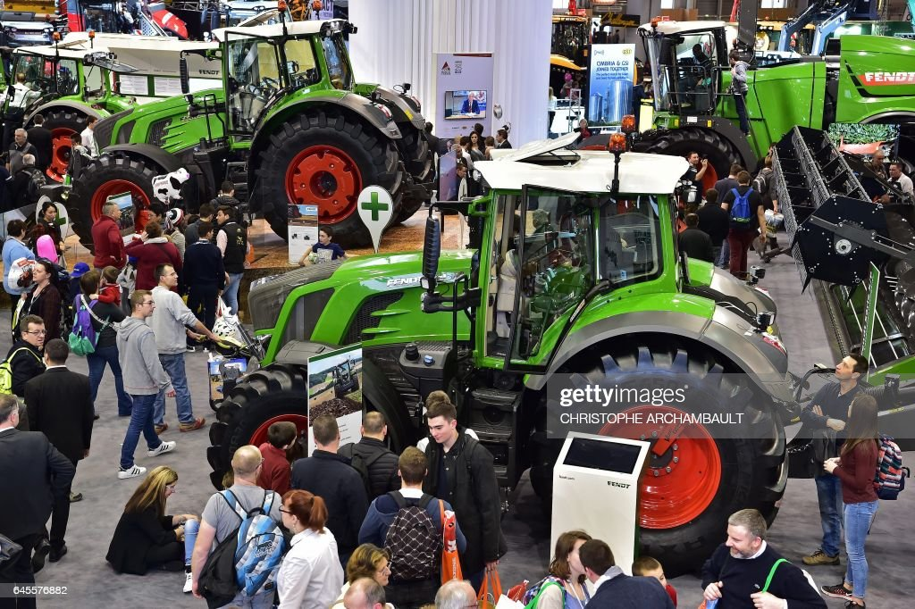Visitors walk past tractors displayed during the SIMA, Paris International agribusiness show at the Parc des Expositions Paris Nord in Villepinte on February 26, 2017. / AFP / CHRISTOPHE