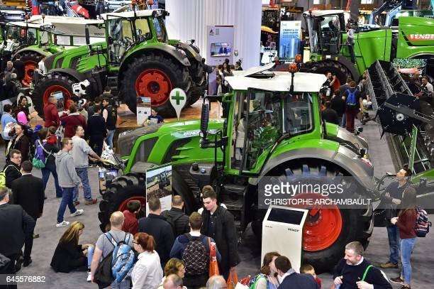 Visitors walk past tractors displayed during the SIMA Paris International agribusiness show at the Parc des Expositions Paris Nord in Villepinte on...