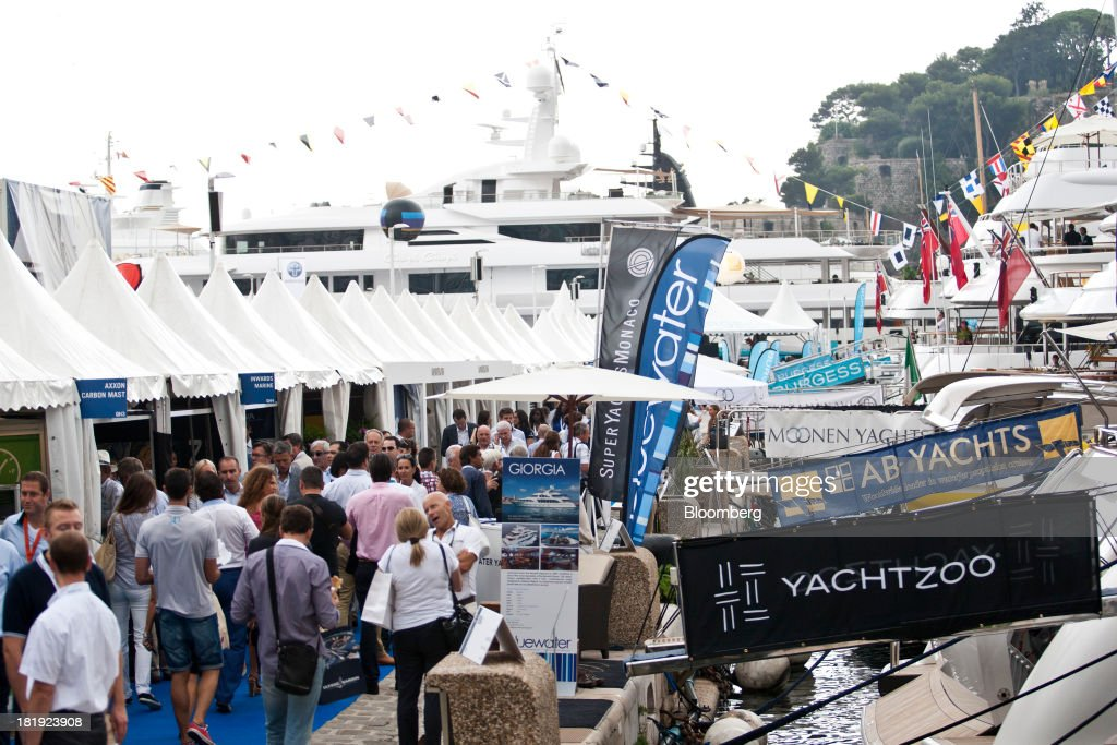 Visitors walk past trade stands on the harbor during the Monaco Yacht Show (MYS) in Monaco, France, on Thursday, Sept. 26, 2013. Over 100 of the world's luxury yachts will be displayed in Port Hercules during the 23rd MYS which runs from Sept. 25 - 28. Photographer: Balint Porneczi/Bloomberg via Getty Images