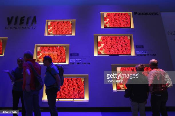 Visitors walk past vibrant Viera LED monitors at the Panasonic stand at the 2014 IFA home electronics and appliances trade fair on September 5 2014...
