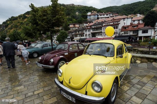 Visitors walk past vintage cars displayed during the 12th Old Timer Fest on July 17 2017 in the historic city of Prizren in southern Kosovo / AFP...