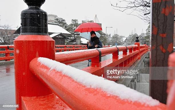 Visitors walk snowcovered Nakabashi bridge on December 5 2014 in Takayama Gifu Japan A wintry atmospheric pressure pattern triggers snowfall across...