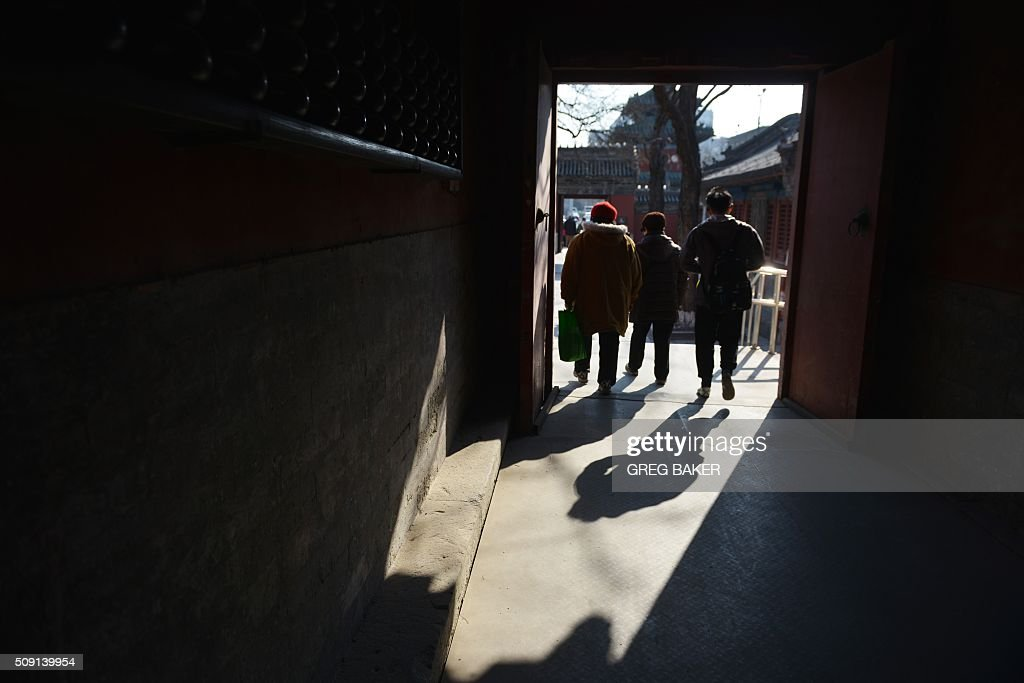 Visitors walk through a temple in Beijing during Lunar New Year celebrations on February 9, 2016. Millions of Chinese are celebrating Spring Festival, the most important holiday on the Chinese calendar, which this year marks the beginning of the Year of the Monkey. AFP PHOTO / GREG BAKER / AFP / GREG BAKER