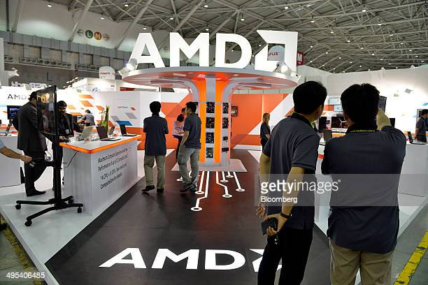 Visitors walk through the Advanced Micro Devices Inc booth at the Computex Taipei 2014 expo at the Taipei Nangang Exhibition Center in Taipei Taiwan...