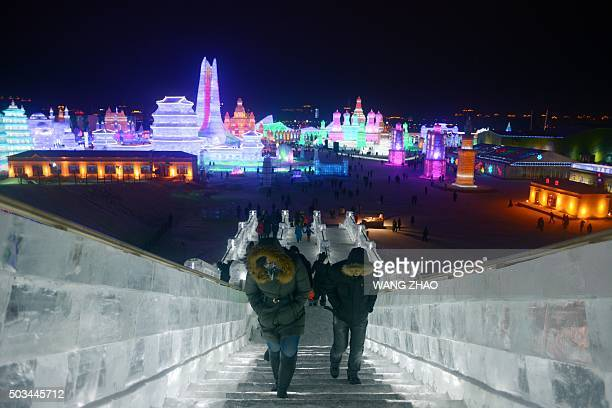 Visitors walk through the China Ice and Snow World during the Harbin International Ice and Snow Festival in Harbin northeast China's Heilongjiang...