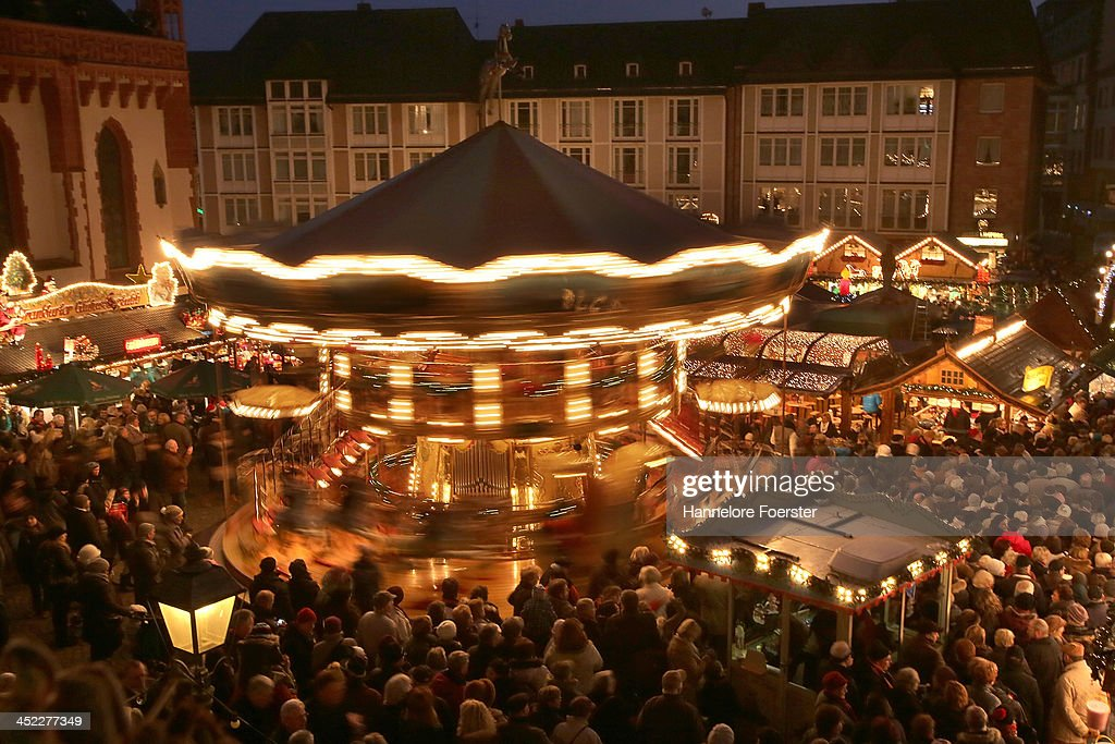 Visitors walk through the Christmas market at Roemerberg square on its opening day on November 27, 2013 in Frankfurt, Germany. Christmas markets, which traditionally sell mulled wine, stollen cake, Christmas tree ornaments and other crafts and are an essential part of German Christmas tradition, open across the country this week.