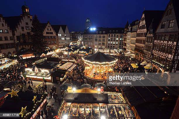 Visitors walk through the Christmas market at Roemerberg square on its opening day on November 26 2014 in Frankfurt Germany Christmas markets which...