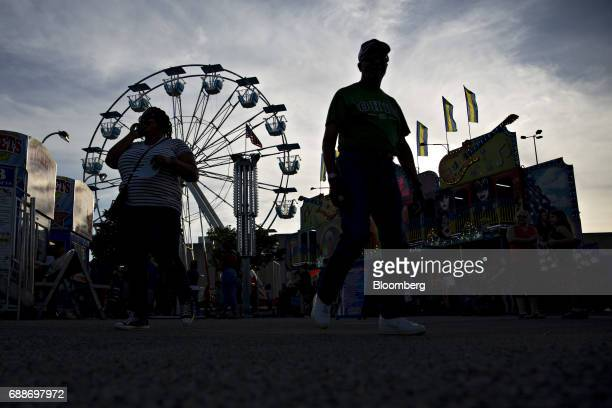 Visitors walk through the Dreamland Amusements carnival in the parking lot of the Marley Station Mall in Glen Burnie Maryland US on Friday April 28...