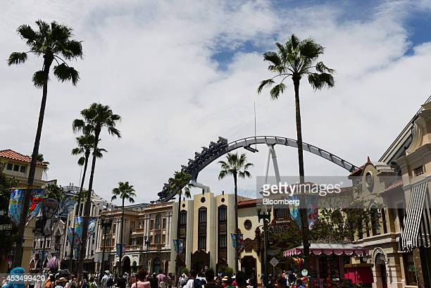 Visitors walk through the Universal Studios Japan operated by USJ Co in Osaka Japan on Thursday Aug 7 2014 USJ is counting on its cachet turning...