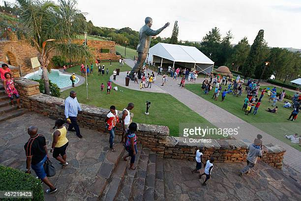 Visitors walk to see the statue of former South African President Nelson Mandela that was unveiled at the Union Buildings on December 16 2013 in...
