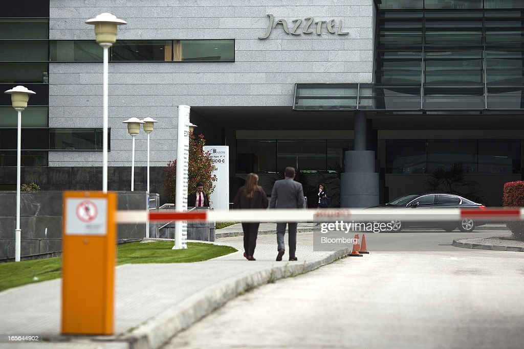 Visitors walk towards the entrance to the offices of Jazztel Plc in Alcobendas, Spain, on Thursday, April 4, 2013. Jazztel almost doubled its share of the Spanish broadband market from 2009 to 2012 as it focused mostly on the fixed-telephone business through a reliable and affordable product that has gained popularity among debt-strapped Spaniards. Photographer: Angel Navarrete/Bloomberg via Getty Images
