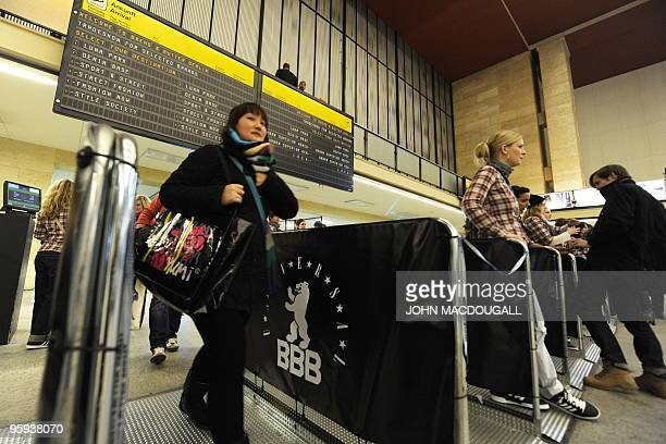 Visitors walk under a flight schedule display as they enter Tempelhof airport's main hall during the Bread and Butter international trade fair for...