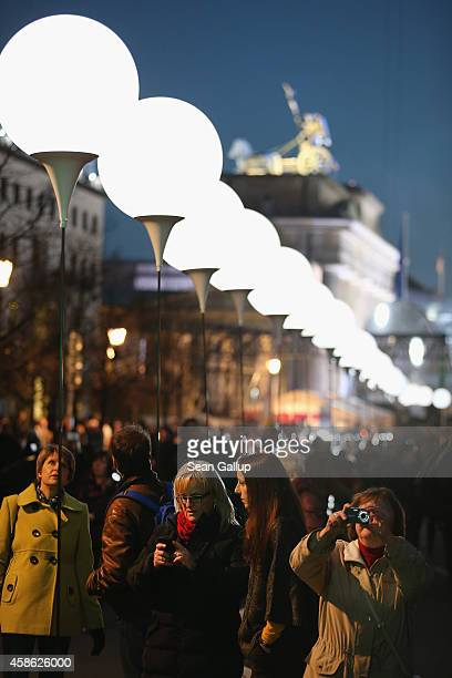 Visitors walk under a light installation of balloons tethered to lamps along the course of the former Berlin Wall near the Brandenburg Gate on the...