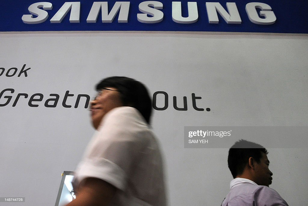 Visitors walk under a Samsung logo during the Computex 2012 in Taipei on June 5, 2012. Taiwan PC makers Acer and Asus took another shot at gaining a foothold in the tablet market, unveiling several new products running on Microsoft's much-anticipated Windows 8 operating system. AFP PHOTO / Sam YEH