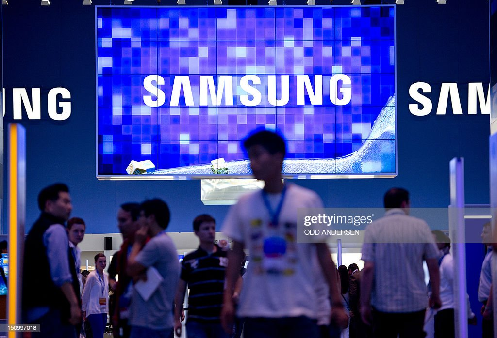 Visitors walk underneath a giant oled TV screen at the Samsung booth at the 52nd edition of the 'IFA' (Internationale Funkausstellung) trade fair in Berlin on August 30, 2012. IFA, Europe's largest consumer electronics and home appliances fair opens to the public from August 31 to September 5, 2012, with more than 1,400 exhibitors unveiling the latest touch-screen tablets, 3D televisions without special glasses and smaller, smarter and more interconnected devices to wow punters.