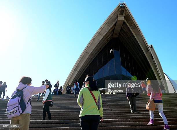 Visitors walk up a flight of steps in front of the Sydney Opera House in Sydney Australia on Saturday July 12 2014 Hotel construction is picking up...