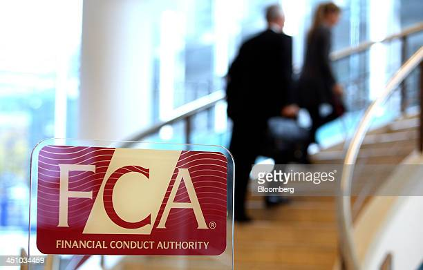 Visitors walk up a staircase as a logo sits on a sign in the reception area of the headquarters of the Financial Conduct Authority in the Canary...
