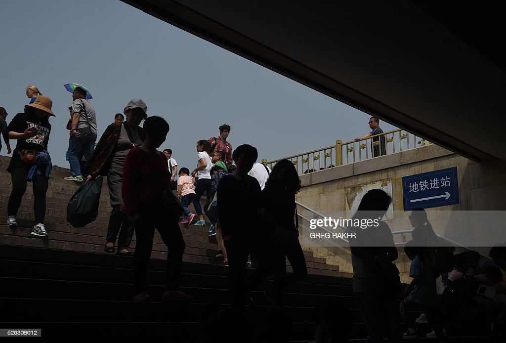 Visitors walk up the steps of an underpass below Beijing's Tiananmen Square on the eve of May Day on April 30, 2016. Millions of people across China are enjoying a three day weekend to mark May Day, on May 1. / AFP / GREG