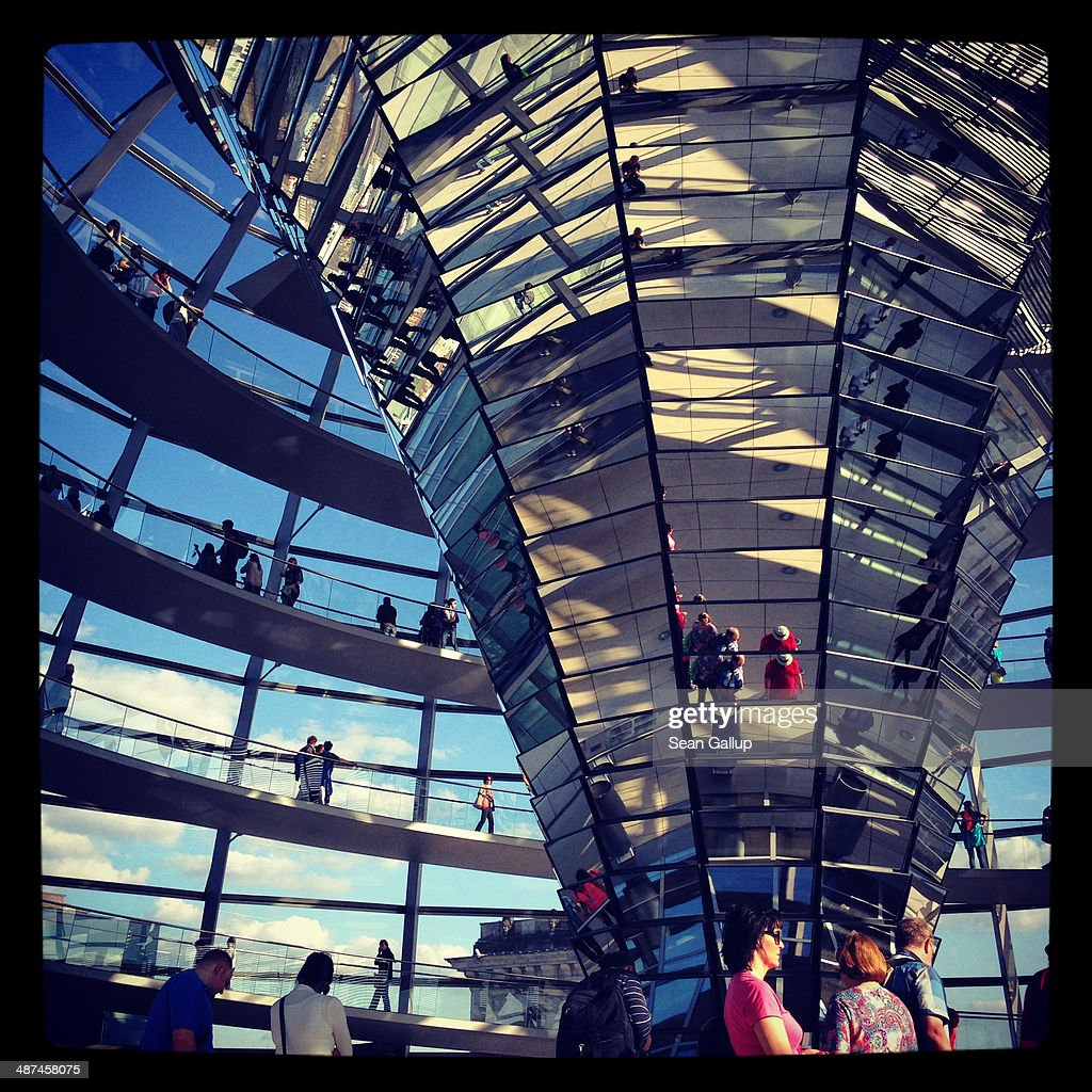 Visitors walk up the winding walkway of the glass and steel cupola as a flag of the European Union flies behind on the roof of the Reichstag on April 28, 2014 in Berlin, Germany. The Reichstag, home of the Bundestag, the German parliament, is among the city's major landmarks and a favourite tourist destination.