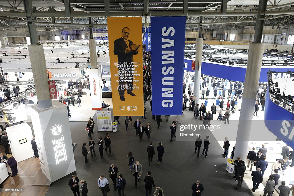 Visitors walks along a hallway past International Business Machines Corp. (IBM), left, and Samsung Electronics Co. signs at the Mobile World Congress in Barcelona, Spain, on Tuesday, Feb. 26, 2013. The Mobile World Congress, where 1,500 exhibitors converge to discuss the future of wireless communication, is a global showcase for the mobile technology industry and runs from Feb. 25 through Feb. 28. Photographer: Simon Dawson/Bloomberg via Getty Images