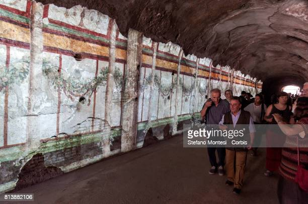 Visitors walks in front of a wall bearing a projection in the Criptoportico Neroniano a tunnel in the Palatino Hill in the Ancient Roman Forum during...