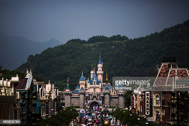 Visitors walks through Main Street USA in front of the Sleeping Beauty Castle center at Walt Disney Co's Disneyland Resort in Hong Kong China on...
