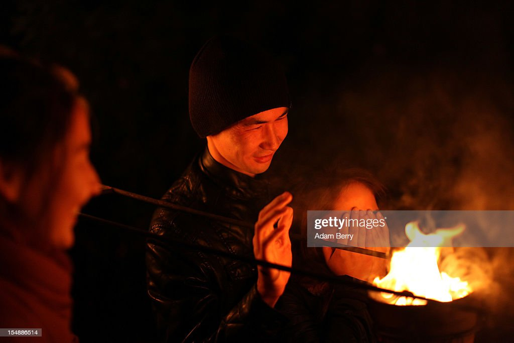 Visitors warm up next to flowerpots full of flames during a presentation by the French fire performers Carabosse as part of celebrations marking the 775th anniversary of the city of Berlin on October 28, 2012 in Berlin, Germany. The settlement of Coelln, which stood opposite Berlin on the Spree river, is first referred to in a document from 1237, and by the beginning of the 14th century Coelln and Berlin joined together to become the region's most important trading center.