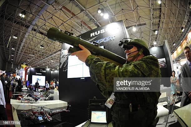 Visitors watch a demonstration of a shoulderlaunched SA18 surfacetoair missile at the Russian Rostec stand during the first day of the LADD defence...