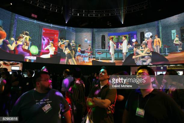 Visitors watch a demonstration of the EA game The Sims 2 on a 360 degree screen at the 11th annual Electronic Entertainment Expo on May 19 2005 in...