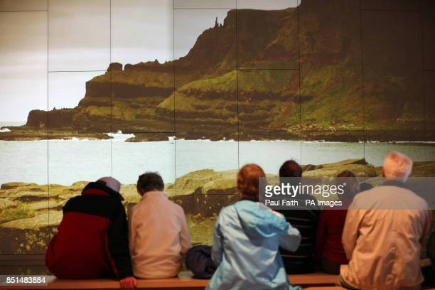 Visitors watch a large video screen on the formation of the Causeway during their visit to the Giant's Causeway Visitor Centre Co Antrim which is...