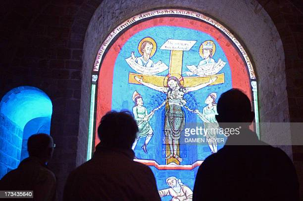 Visitors watch a light show in the Mont SaintMichel abbey as part of its Nocturnes festival on July 11 2013 at the Unesco world heritage site in...