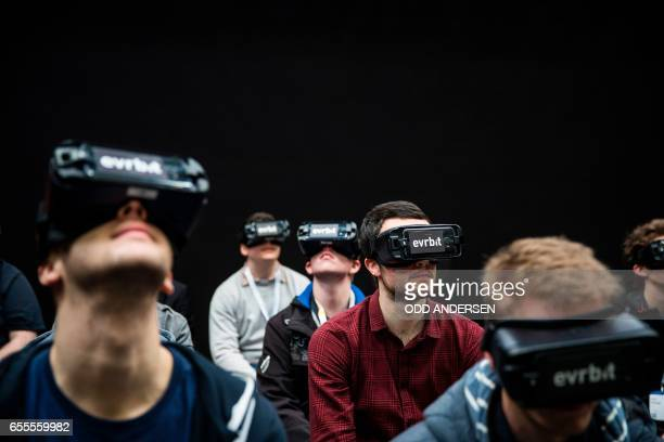 Visitors watch a movie wearing Virtual Reality glasses at the German firm Evrbit booth at the Cebit technology fair in Hannover on March 20 2017 The...