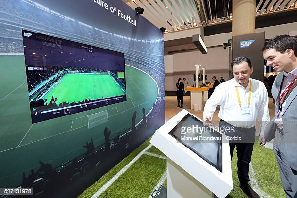 Visitors watch a product demonstration at the SAP AG pavillon SAP is working with the German national football team to prepare for the World Cup in...