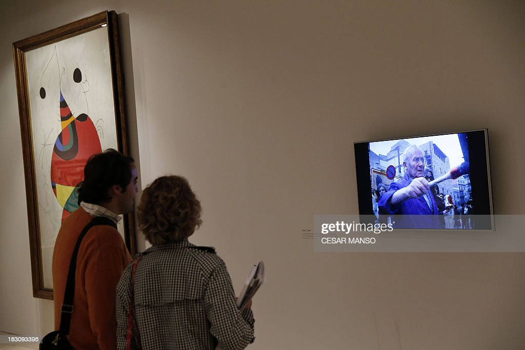 Visitors watch a short film about Spanish artist Joan Miro (1893-1983) during the exhibition 'Miro: the experience of watching' at the Palencia Cathedral in Burgos northern Spain on October 4, 2013. The project, curated by Carmen Belen Fernandez Galan, focuses on works by Miro during the last years of his life when a fundamental change in his creative trajectory is noted. The exhibition will travel to various cities of the US in 2014. AFP PHOTO / CESAR MANSO
