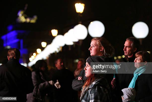 Visitors watch an outdoor screening of a short film about the Berlin Wall in front of the Brandenburg Gate and a section of the light installation...