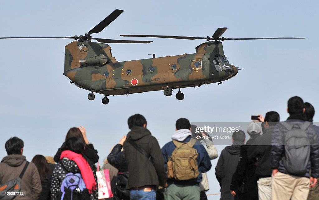 Visitors watch as a Japanese Ground Self Defense Force helicopter flies over ground troops taking part in a new year military drill at the training grounds in Narashino, suburban Tokyo on January 13, 2013. A total of 300 personnel, 20 aircraft and 33 vehicles took part in the open exercise at the defense force's Narashino training ground. AFP PHOTO / KAZUHIRO NOGI