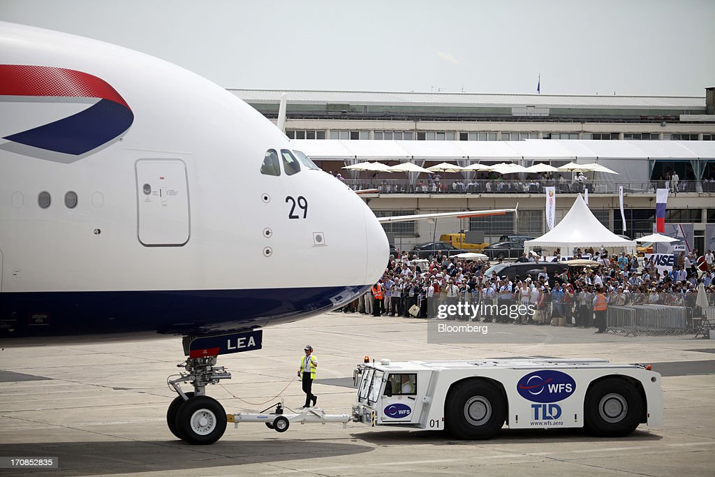 Visitors watch as an aircraft tractor pulls an Airbus SAS A380 aircraft, operated by British Airways, on the second day of the Paris Air Show in Paris, France, on Tuesday, June 18, 2013. The 50th International Paris Air Show is the world's largest aviation and space industry show, and takes place at Le Bourget airport June 17-23. Photographer: Balint Porneczi/Bloomberg via Getty Images