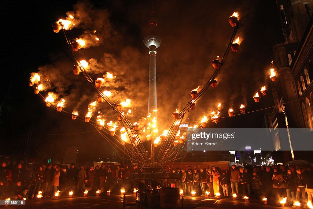 Visitors watch as an animated frame shaped like a flower covered in flowerpots full of flames opens and closes in front of the Fernsehturm (Television Tower) during a presentation by the French fire performers Carabosse as part of celebrations marking the 775th anniversary of the city of Berlin on October 28, 2012 in Berlin, Germany. The settlement of Coelln, which stood opposite Berlin on the Spree river, is first referred to in a document from 1237, and by the beginning of the 14th century Coelln and Berlin joined together to become the region's most important trading center.