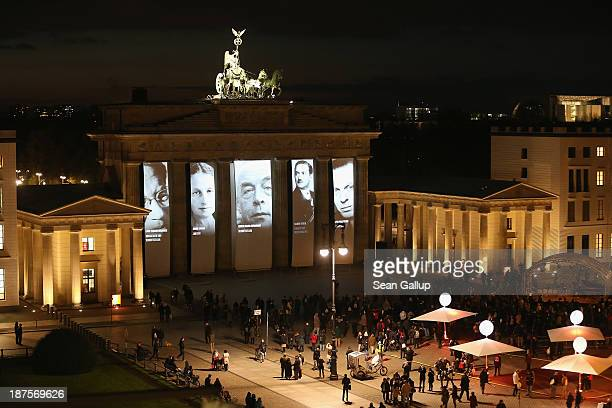 Visitors watch as portraits of Berlin Jewish actors intellectuals artists academics athletes and others who were persecuted by the Nazis in the 1930s...