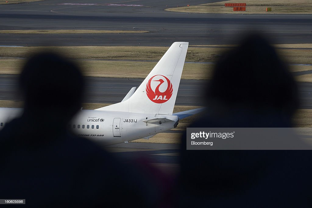 Visitors watch from an observation deck as a Boeing Co. 737 aircraft operated by Japan Airlines Co. (JAL) stands parked at Haneda Airport in Tokyo, Japan, on Sunday, Feb. 3, 2013. Japan Airlines, the nation's largest carrier by market value, is scheduled to release earnings on Feb. 4. Photographer: Akio Kon/Bloomberg via Getty Images