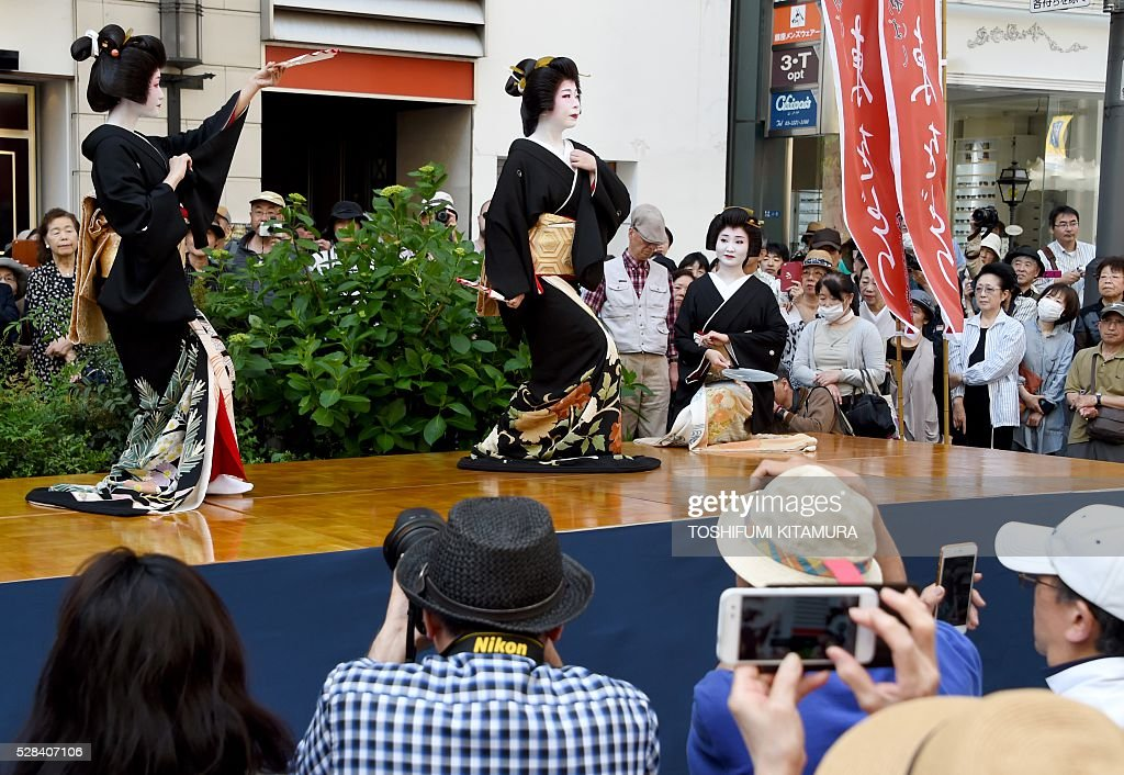 Visitors watch geishas performing a traditional dance on a stage during the Ginza 'Yanagi' festival at the Ginza shopping district in Tokyo on May 5, 2016. Geishas working in the area displayed their skills for holiday shoppers to promote their 'Azuma Odori,' a traditional dance event taking place later this month. / AFP / TOSHIFUMI