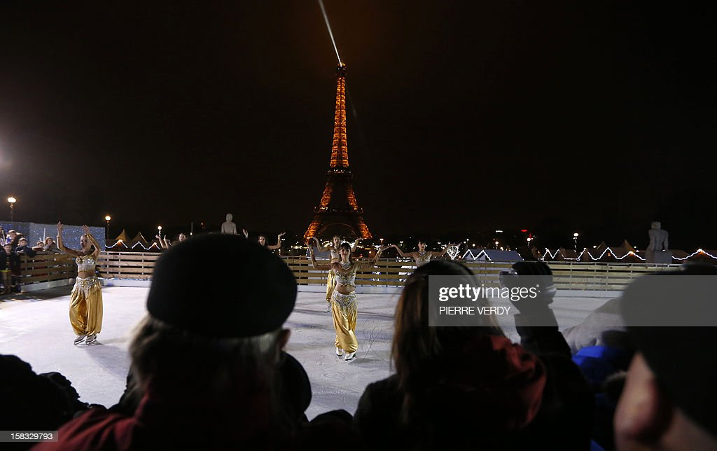 Visitors watch ice skaters performing dances during the inauguration of the 'Christmas village', on December 13, 2012, in Paris, as part of the 'Trocadero On Ice' event. An ice-skating rink opened to public in front of the Eiffel tower, and will run until January 6, 2013.